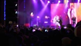 Muchedumbre que hace el partido en un concierto de rock Cámaras del control de las manos con los indicadores digitales almacen de video
