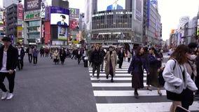 Muchedumbres de gente que camina a través en la calle que cruza famosa de Shibuya en Tokio, Japón almacen de metraje de vídeo