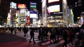 Muchedumbres de gente que camina a través en la calle que cruza famosa de Shibuya en Tokio en la noche, Japón almacen de metraje de vídeo