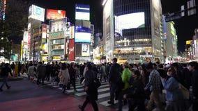 Muchedumbres de gente que camina a través en la calle que cruza famosa de Shibuya en Tokio en la noche, Japón metrajes