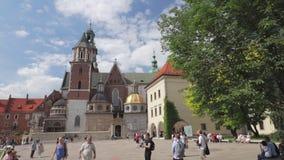 Muchedumbres de turistas internacionales que pasan cerca en el patio del castillo real de Wawel metrajes