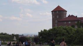 Muchedumbres de turistas internacionales que pasan cerca en el patio del castillo real de Wawel almacen de video