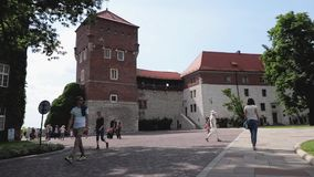 Muchedumbres de turistas internacionales que pasan cerca en el patio del castillo real de Wawel almacen de metraje de vídeo