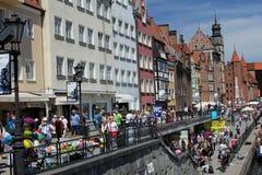 Muchedumbres de turistas que caminan abajo de la calle de la ciudad vieja de Gdansk en el río de Motlawa, Polonia Imágenes de archivo libres de regalías