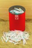 Mucho aguja en cajas de disposición rojas en backgroun marrón de la tela del saco Fotografía de archivo