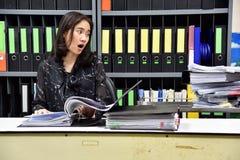 Mucho concepto del trabajo y del funcionamiento duro, oficinista asiático chocó sobre la porción de papeleo imagenes de archivo