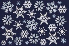 Mucho copo de nieve blanco pintado con la pintura a través de una plantilla en un fondo azul marino Fotografía de archivo