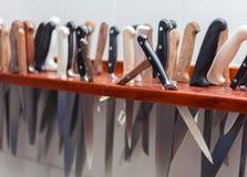Mucho cuchillo grande que cuelga almacenamiento de madera en la cocina del restaurante Imágenes de archivo libres de regalías