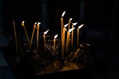 Mucho de velas ardientes en una iglesia Fotografía de archivo