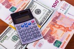 Mucho dinero en diversas monedas y calculadora Fotografía de archivo libre de regalías