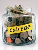 Mucho dinero en un tarro de cristal etiquetó la universidad Foto de archivo