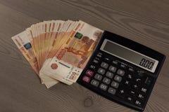 Mucho dinero y calculadora rusos en un fondo de madera Imagen de archivo
