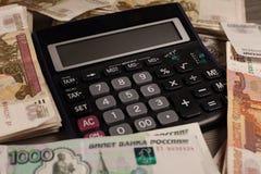 Mucho dinero y calculadora rusos en un fondo de madera Fotos de archivo libres de regalías