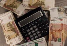 Mucho dinero y calculadora rusos en un fondo de madera Imágenes de archivo libres de regalías