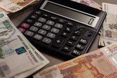 Mucho dinero y calculadora rusos en un fondo de madera Foto de archivo