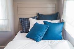 Mucho dormitorio azul y blanco con la luz caliente de la ventana Foto de archivo