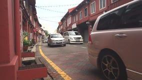 Mucho edificio histórico rojo famoso del coche del canal turístico de la impulsión en Malaca metrajes