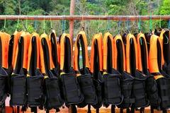 Mucho ejecución anaranjada del chaleco salvavidas o del chaleco de vida en línea de ropa Fotografía de archivo libre de regalías