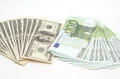 Mucho euro y dólares en el fondo blanco Imagenes de archivo
