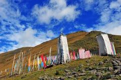 Mucho rezo del tibetano señala el vuelo por medio de una bandera con la mandala en la ladera Imagenes de archivo