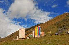 Mucho rezo del tibetano señala el vuelo por medio de una bandera con la mandala en la ladera Fotos de archivo
