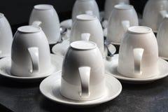 Mucho tazas blancas del té y de café en fondo negro Fotos de archivo