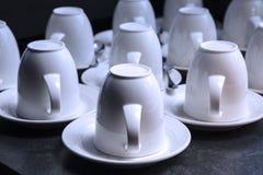 Mucho tazas blancas del té y de café en fondo negro Fotografía de archivo