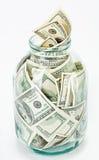 Muchos 100 billetes de banco de dólar americano en un tarro de cristal Fotografía de archivo libre de regalías