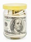Muchos 100 billetes de banco de dólar americano en un tarro de cristal Imagen de archivo libre de regalías