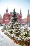 Muchos abetos en la nieve son soporte el cuadrado cerca del edificio histórico del museo Imagen de archivo libre de regalías