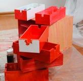 Muchos apilados recientemente pintaron las cajas de madera y las latas rojas de la pintura en piso fotos de archivo