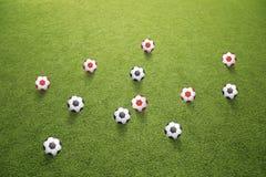 Muchos balones de fútbol negros y rojos en hierba Foto de archivo libre de regalías