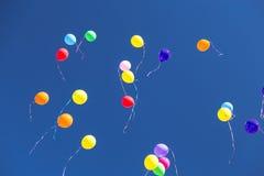 Muchos baloons brillantes en el cielo azul Foto de archivo