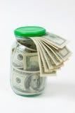 Muchos 100 billetes de banco de dólar americano en un tarro de cristal aislado en el fondo blanco Foto de archivo libre de regalías