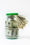 Muchos 100 billetes de banco de dólar americano en un tarro de cristal aislado en el fondo blanco Fotografía de archivo libre de regalías