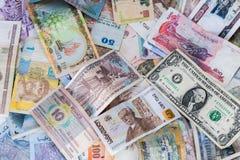 Muchos billetes de banco de los países diferentes dispersaron en la tabla imagen de archivo