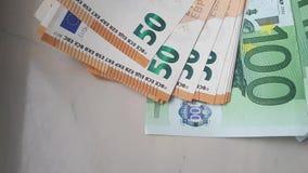 Muchos 50, 100 billetes de banco del euro que se deslizan en un marco almacen de video