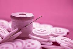 Muchos botones redondos rosados mienten en una superficie plana en la bobina del fondo con los hilos de lino foto de archivo