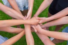Muchos brazos de los niños que llevan a cabo las manos juntas Imagenes de archivo