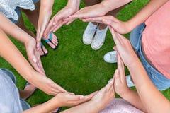 Muchos brazos de niños con las manos que hacen el círculo Imagenes de archivo