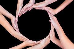 Muchos brazos de niños con las manos que hacen el círculo en negro Foto de archivo libre de regalías