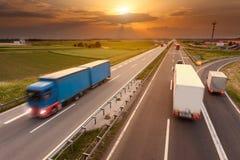Muchos camiones en la falta de definición de movimiento en la carretera en la puesta del sol Foto de archivo