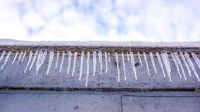 Muchos carámbanos largos verticales claros en el tejado con la pared de ladrillo blanca contra el cielo azul soleado con las nube Imagen de archivo libre de regalías