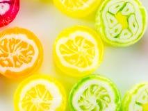 Muchos caramelos redondos coloridos y deliciosos en una placa Imágenes de archivo libres de regalías