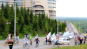 Muchos ciclistas y caminante van a lo largo del camino Colina cubierta con los árboles de la hierba verde y de la piel Desfile de almacen de metraje de vídeo