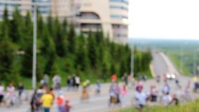 Muchos ciclistas y caminante van a lo largo del camino Vídeo acelerado El coche va abajo de altura metrajes