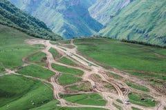 Muchos coches que se mueven a lo largo de un camino de tierra en las montañas fotos de archivo