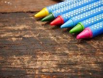 Muchos colorean el creyón en el tablero de madera imágenes de archivo libres de regalías