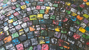 Muchos colorearon el pavimento pintado de la piedra del adoquín adentro después de lluvia Foto de archivo libre de regalías