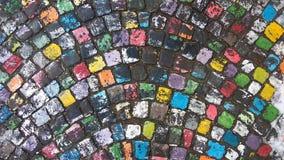 Muchos colorearon el pavimento pintado de la piedra del adoquín adentro después de lluvia Imágenes de archivo libres de regalías